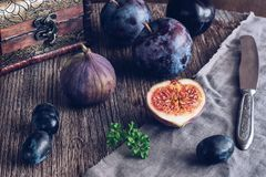 Die Feige wird auf einen Holztisch mit Trauben und Pflaumen geschnitten Noch Leben mit Feigen Selektiver Fokus stockbilder