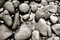 Die Felsen, die schwarzen Sand bilden, setzen auf Maui, Hawaii auf den Strand Lizenzfreie Stockfotografie