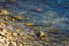 Die felsige Küstenlinie und die Felsen unter dem Wasser Stockfotografie