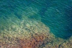 Die felsige Küstenlinie und die Felsen unter dem Wasser Lizenzfreies Stockbild