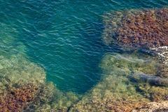 Die felsige Küstenlinie und die Felsen unter dem Wasser Lizenzfreie Stockfotografie