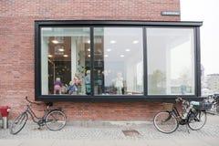 Die Fenster des Kindergartens in einem modernen Gebäude und in den Fahrrädern nahe der Wand lizenzfreies stockfoto