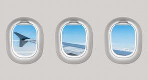 Die Fenster einer Fläche zum Flugzeugflügel und zum clou heraus schauen Stockfoto