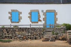 Die Fensterläden dieses Hauses, das in Bretagne, Frankreich aufgestellt wurde, wurden im Blau gemalt Lizenzfreie Stockbilder