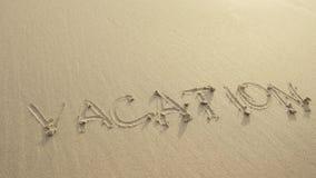 Die FERIEN, die auf den Strandsand geschrieben wurden, wuschen sich immer durch Wellen stockfotos