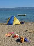 Die Ferienpaare, die auf Sand kampieren, setzen nahe Boot auf den Strand Lizenzfreie Stockfotos
