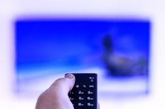 Die Fernbedienung ist in der Hand eines Mannes, verwiesen auf ein Großbild-Fernsehen lizenzfreie stockfotos