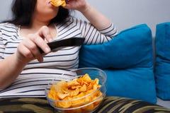 Die fette überladene Frau, die auf dem Sofa sitzt, essend bricht während wat ab Stockfotos