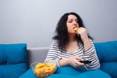 Die fette überladene Frau, die auf dem Sofa sitzt, essend bricht während wat ab Lizenzfreie Stockbilder