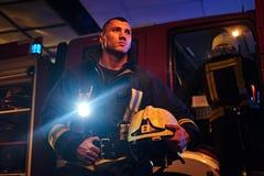 Die Feuerwehr kam zum Anruf nachts Der hübsche Feuerwehrmann, der eine schützende Uniform mit einer Taschenlampe trägt, schloss e stockfoto