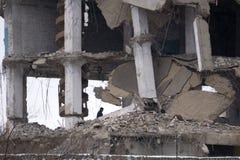 Die Feuerwehrmänner, die Rettung tun, arbeiten über dem gebrannten Bauschutt Stockbild