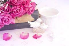 Die Figürchen, die Tauben im Liebe Valentinsgrußblumenstrauß von rosa Rosen auf Blumenhintergrund der alten Bücher heiraten, ist  Stockbilder