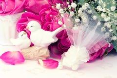 Die Figürchen, die Tauben im Liebe Valentinsgrußblumenstrauß von rosa Rosen auf Blumenhintergrund der alten Bücher heiraten, ist  Stockfotografie