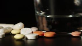 Die Finger des Mannes nehmen Pillen eine und transparentes Glas Wasseraufstiege und senken dann - Makro stock video