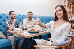 Die Firma von jungen Kerlen und von Mädchen in einem Café, das Mädchen lächelt und zeigt sich ihren Daumen stockfoto