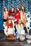 Die Firma von sechs schönen Mädchen auf dem Hintergrund von Christma Stockfotos