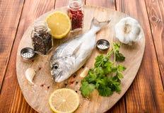 Die Fische mit Gemüse auf einem hölzernen Brett Lizenzfreie Stockfotografie