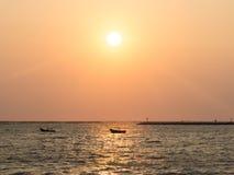 Die Fischer, die auf einem Bootsschattenbild im Abendsonnenuntergang fischen, beleuchten stockfotografie