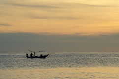 Die Fischer, die auf einem Bootsschattenbild im Morgensonnenaufgang fischen, beleuchten stockbilder