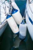 Die Flöße, die zu einer weißen Yacht befestigt wurden, machten am Hafen fest Stockbild