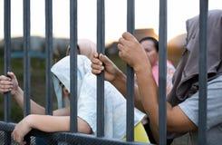 Die Flüchtlingsvölkerhand, die Metallstange auf Flüchtlingslagerstandort hält, sitzen stockbild