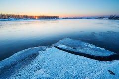 Die Flüsse bedeckt mit Eissonnenuntergang Lizenzfreies Stockbild