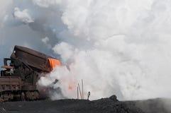 Die flüssige flüssige Schlacke und eine Wolke des heißen Dampfs stockfotografie