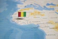 Die Flagge der Guine in der Weltkarte stockbild