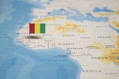 Die Flagge der Guine in der Weltkarte lizenzfreies stockbild
