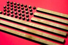 Die Flagge der Vereinigten Staaten auf einem roten Hintergrund gemacht vom Holz, goldene Streifen auf einem roten Hintergrund stockfotos