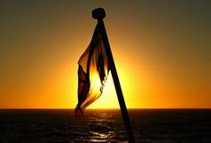 Die Flagge des Schiffs bei Sonnenuntergang lizenzfreie stockfotos