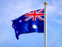 Die Flagge von Australien wellenartig bewegend über blauen Himmel Lizenzfreies Stockfoto