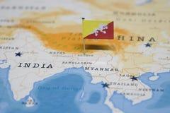Die Flagge von Bhutan in der Weltkarte stockbild