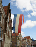 Die Flagge von den Niederlanden fliegt über eine Straße in der Hafenstadt von Hoorn, lizenzfreie stockbilder