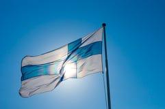 Die Flagge von Finnland entwickelt sich vor dem hintergrund des blauen Himmels lizenzfreies stockfoto