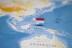 Die Flagge von Indonesien in der Weltkarte stockfotografie