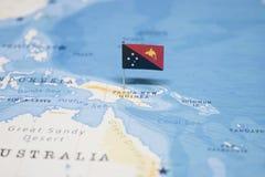 Die Flagge von Papua-Neu-Guinea in der Weltkarte lizenzfreies stockbild