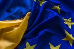 Die Flagge von Ukraine und die Flagge der Europäischen Gemeinschaft werden zusammen gesponnen Stockbilder