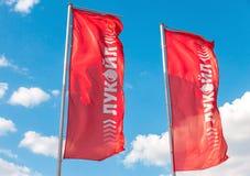 Die Flaggen des Ölkonzerns Lukoil gegen den blauen Himmel Lizenzfreie Stockfotos
