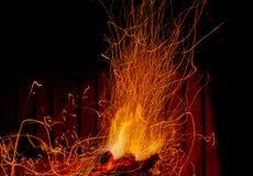 Die Flamme in der Dunkelheit mit Funken Stockfotografie
