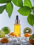 Die Flasche des kosmetischen befeuchtenden Öls der Frucht mit weißen Steinen und Früchten Stockfotos