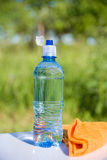 Die Flasche des Wassers und des Tuches Stockfoto