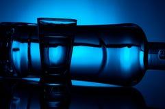 Die Flasche Wodka liegend mit Glas beleuchtete mit blauer Hintergrundbeleuchtung Lizenzfreies Stockbild
