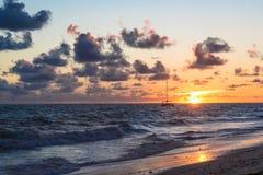 Die flaumigen dunklen Wolken, die über turbulentes Ozeanwasser auf sandigem Strand schwimmen, stützen unter stockbild
