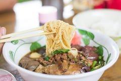 Die Fleisch fressenden thailändischen Hühnernudeln Stockfoto