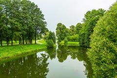 Die Flussbänke werden mit grünem Gras und grünen Bäumen herein bedeckt Stockbild