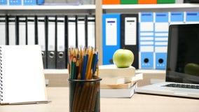 Die Fokusspurhaltung summen herein Gesamtlänge auf grünem Apfel, farbigen Bleistiften und Papiernotizbuch laut stock video