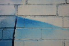 Die Fotografie malte weiße Backsteinmauer mit einem Fragment des Graffitiblaus mit schwarzer Linie Lizenzfreie Stockfotos