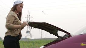 Die Frau öffnet die Haube eines Autos stock video