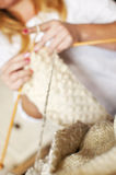 Die Frau übergibt das Handeln der Wolle strickend in einer sehr flachen Schärfentiefe Lizenzfreie Stockfotos